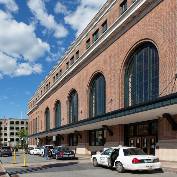 Brick rail station featuring large round arch windows and entryways.