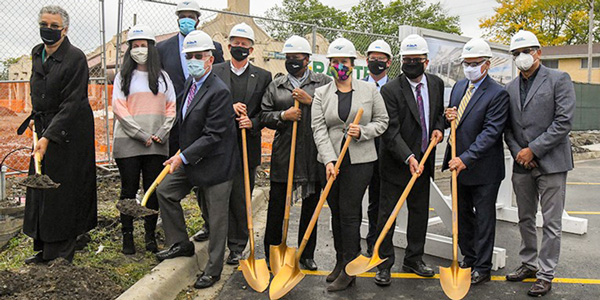 Group of men and women with shovels and hardhats